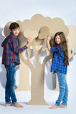 Boy with girl hiding behind cardboard tree and holding a heart. Love concept Stock Images