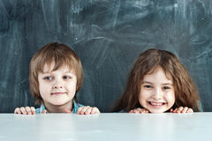Boy and girl hiding behind a table Royalty Free Stock Images