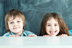 Boy and girl hiding behind a table near the school board Stock Photo
