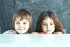 Boy and girl hiding behind a table near the school board Royalty Free Stock Photo