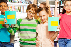 Boy and girl hold exercise books in library Stock Images