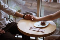Boy and girl hold hands in cafe stock images