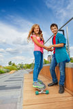 Boy and girl hold hands when she rides skateboard Royalty Free Stock Images