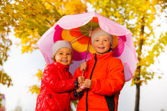 Boy and girl hold umbrella together under rain Stock Photos
