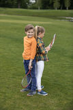 Boy and girl holding badminton racquets while standing back to back on green grass. Adorable boy and girl holding badminton racquets while standing back to back royalty free stock photo