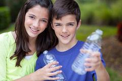 Boy and girl holding clear bottle for recycling Stock Photos