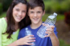 Boy and girl holding clear bottle for recycling Royalty Free Stock Photography