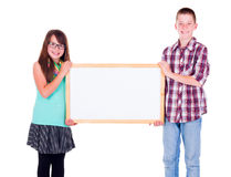 Boy and girl holding an empty advertising board Stock Images