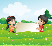 A boy and a girl holding an empty cardboard Royalty Free Stock Image