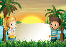 A boy and a girl holding an empty signboard Royalty Free Stock Images