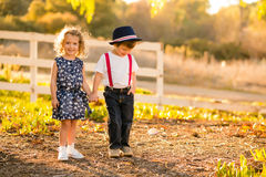 Boy and Girl holding hands. With back lighting in a farm setting Royalty Free Stock Image