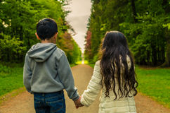 Boy & Girl Holding Hands Facing Path to Distance stock photo