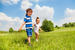 Boy and girl holding hands playing together Stock Images