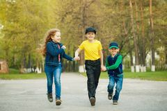 Boy and girl holding hands and running in a park. Stock Images