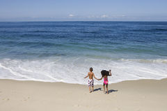 Boy and girl (5-7) holding hands on sandy beach near water's edge, Atlantic Ocean in background, rear view Royalty Free Stock Image