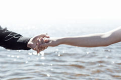 Boy and girl are holding hands on the sea Stock Photo