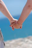 Boy and girl holding hands. Small boy and girl holding hands on a hill looking down on a sea Royalty Free Stock Photography