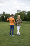 Boy and girl holding hands while standing on green field, boy holding badminton racquet on his shoulder Stock Images
