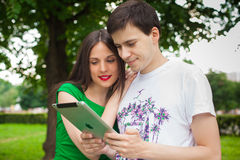 Boy and girl holding ipad together outdoor in the park. Boy and girl in green dress holding ipad together outdoor in the park Stock Photography