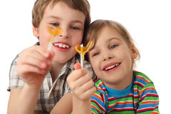 Boy and girl holding lollipops ,looking on it Royalty Free Stock Image