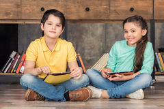 Boy and girl holding tablets in hands in library stock photos