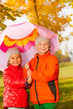 Boy with girl holding umbrella together and stand Stock Photos