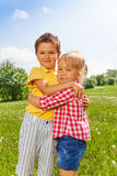 Boy and girl hugging in green field Stock Photos
