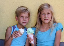 Boy and girl with ice cream. Sweet 8-year-old boy and pretty 11-year-old girl eating ice cream Royalty Free Stock Images