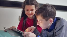 Boy and a girl indoors kids are playing a tablet. brother and sister children social media online games in the tablet. Boy and girl indoors kids are playing a stock video