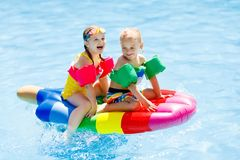 Kids on inflatable float in swimming pool. Boy and girl on inflatable ice cream float in outdoor swimming pool of tropical resort. Summer vacation with kids Stock Photography