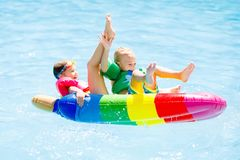 Kids on inflatable float in swimming pool. Boy and girl on inflatable ice cream float in outdoor swimming pool of tropical resort. Summer vacation with kids Stock Image