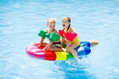 Kids on inflatable float in swimming pool. Boy and girl on inflatable ice cream float in outdoor swimming pool of tropical resort. Summer vacation with kids Stock Photos