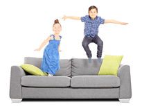 Boy and a girl jumping on the couch. Isolated on white background Royalty Free Stock Images