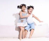 Boy and girl jumping and laughing on sofa royalty free stock photo