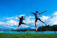 Boy and girl jumping into the pool in the lake. Stock Photos