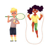 Boy and girl with jumping rope, badminton racket at playground. Black African girl and Caucasian boy playing with jumping rope and badminton racket at playground Stock Images