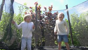 Boy and girl jumping on trampoline in house backyard. Handheld shot. Boy and girl jumping on trampoline in house backyard. Happy children have fun. Handheld stock video