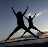Boy and girl jumping up. At different levels on the background of the sunset sky with clouds - the symbol of victory success and achieving Royalty Free Stock Images