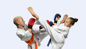 Boy and girl in karategi perform paired exercises Stock Photos