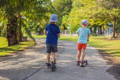 Boy and girl on kick scooters in park. Kids learn to skate roller board. Little boy skating on sunny summer day. Outdoor. Activity for children on safe stock photo
