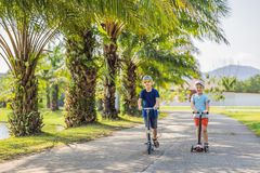 Boy and girl on kick scooters in park. Kids learn to skate roller board. Little boy skating on sunny summer day. Outdoor. Activity for children on safe royalty free stock images