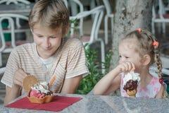 Boy and girl kids enjoying their Italian ice cream in gelateria. Boy and girl kids are enjoying their Italian ice cream in gelateria Stock Image