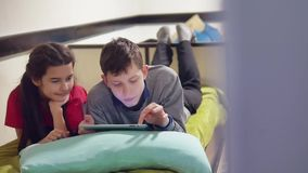 Boy and a girl kids are playing a tablet. brother and sister children social media online games indoors in the tablet. Boy and a girl kids are playing tablet stock footage