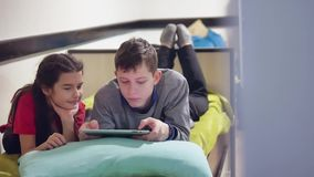 Boy and a girl kids are playing a tablet. brother and sister children social media online games in the tablet indoors. Boy and a girl kids are playing tablet stock footage