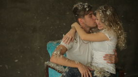 Boy and girl kissing on chair, feathers stock footage