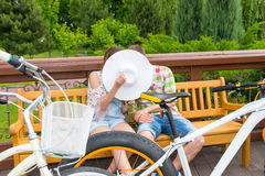 Boy and girl kissing hiding behind the hat while sitting on a be. Nch parked their bikes opposite themselves in a park Stock Image