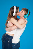 Boy and girl kissing, wearing headphones in the studio Royalty Free Stock Photo