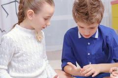 Boy and girl knit a bracelet Royalty Free Stock Photos