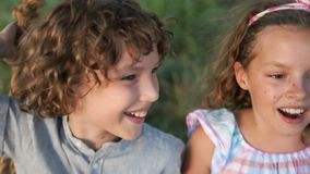 The boy and the girl laughed, swinging on the swings. There are white healthy teeth, white-toothed smiles of children