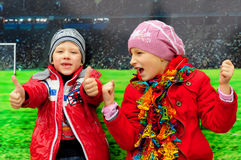 Boy with a girl laughing in the background of a football field Stock Photo